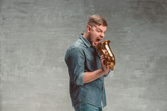 Happy saxophonist with sax over gray background Royalty Free Stock Photography