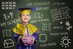 Happy scholar dressed toddler with piggybank. Happy scholar dressed toddler carrying a piggybank Royalty Free Stock Photography