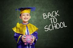 Happy scholar dressed toddler with piggybank Royalty Free Stock Image