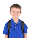 Happy School Boy with Bookbag. A young school boy is wearing a blue shirt on a white isolated background. He has a book bag and looks happy Royalty Free Stock Image