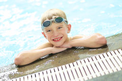 Happy school boy with goggles in swimming pool Stock Images