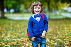 Happy school boy holding his bag and smiling Stock Image