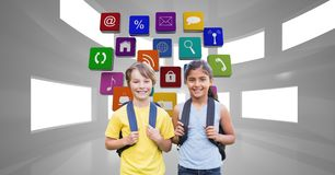 Happy school children carrying backpacks with application icons in background Royalty Free Stock Images