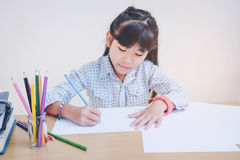 Happy school children drawing with crayons Stock Photo