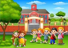 Happy school children standing in front of school building Royalty Free Stock Images