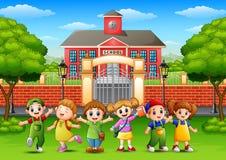 Happy school children standing in front of school building Stock Photography
