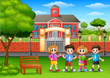 Happy school children standing in outside the front of school building Royalty Free Stock Photography