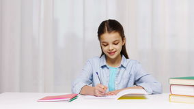 Happy school girl with books and notepad at home stock video footage