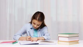 Happy school girl with books and notepad at home stock video