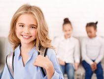 Happy school girl with classmates on background. Happy school girl carrying backpack with classmates on background stock image