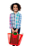 Happy school girl carrying stationery in basket Royalty Free Stock Photography