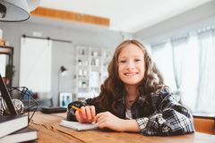 Happy school girl doing homework. Smart child working hard and writing royalty free stock photo