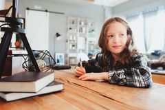 Happy school girl doing homework. Smart child working hard and writing royalty free stock image