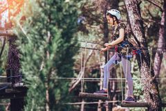Happy school girl enjoying activity in a climbing adventure park. On a summer day stock photography