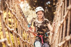 Happy school girl enjoying activity in a climbing adventure park. On a summer day stock images