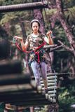 Happy school girl enjoying activity in a climbing adventure park. On a summer day royalty free stock photo