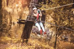 Happy school girl enjoying activity in a climbing adventure park. On a summer day royalty free stock image