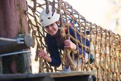 Happy school girl enjoying activity in a climbing adventure park Stock Photos