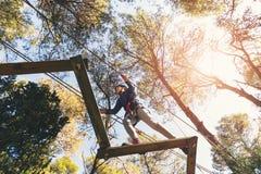 Happy school girl enjoying activity in a climbing adventure park. On a summer day stock photos