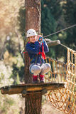 Happy school girl enjoying activity in a climbing adventure park Royalty Free Stock Photo