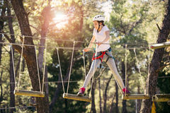 Happy school girl enjoying activity in a climbing adventure park. On a summer day royalty free stock photography