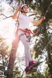 Happy school girl enjoying activity in a climbing adventure park Stock Images