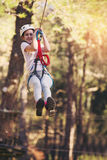 Happy school girl enjoying activity in a climbing adventure park Stock Images
