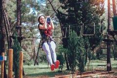 Happy school girl enjoying activity in a climbing adventure park. On a summer day stock photo
