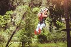 School girl enjoying activity in a climbing adventure park on a summer day. Happy school girl enjoying activity in a climbing adventure park on a summer day royalty free stock photo