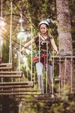 School girl enjoying activity in a climbing adventure park on a summer day. Happy school girl enjoying activity in a climbing adventure park on a summer day stock images