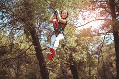 School girl enjoying activity in a climbing adventure park on a summer day. Happy school girl enjoying activity in a climbing adventure park on a summer day stock image