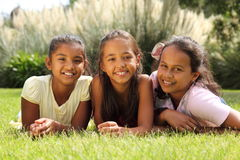 Happy school girl friends lying in grass together stock photo