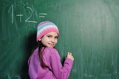 Happy school girl on math classes. Finding solution and solving problems Stock Image