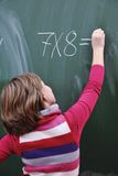 Happy school girl on math classes. Finding solution and solving problems Royalty Free Stock Images