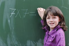 Happy school girl on math classes. Finding solution and solving problems Stock Images
