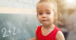 Happy school girl on math classes in kindergarten finding solution and solving problems stock photography