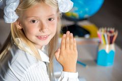 Happy school girl with raised hand Stock Photo