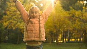 Happy school girl raising arms up, rejoicing beautiful autumn season, fun. Stock photo stock images