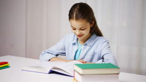 Happy school girl reading book or textbook at home stock footage