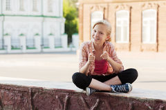 Happy school girl sitting on the city street Stock Photography
