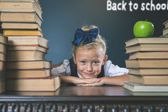 Happy school girl sitting near the table with many books. And one green apple. Back to school. Child dressed in school uniform. Blackboard. Student. Concept of Stock Images