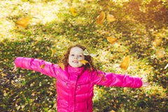 Happy school girl throws the autumn leaves in the air. Instagram Royalty Free Stock Photo