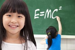 Happy school girls. Happy girls  by chalkboard with e=mc2 Royalty Free Stock Image