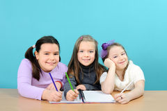 Happy school girls doing their work in classroom. Three happy school girls doing their work in classroom Royalty Free Stock Photos