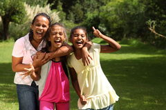 Happy school girls have fun laughing out loud. Three young school girl friends hugging, laughing and having fun in the park giving the thumbs up Royalty Free Stock Photography