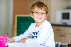 Happy school kid boy with glasses at home making homework Royalty Free Stock Images