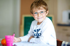 Happy school kid boy with glasses at home making homework Royalty Free Stock Image