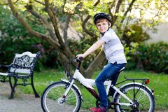Happy school kid boy having fun with riding of bicycle. Active healthy child with safety helmet making sports with bike. In nature. Safety, sports, leisure with royalty free stock photo
