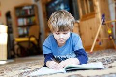 Happy school kid boy at home making homework Stock Photos