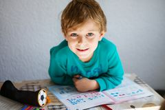 Happy school kid boy at home making homework royalty free stock photography